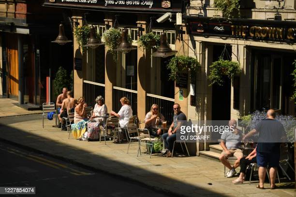 "People enjoy a drink outside a pub in the centre of Manchester, northwest England, on July 31, 2020. - Britain on Friday ""put the brakes on"" easing..."