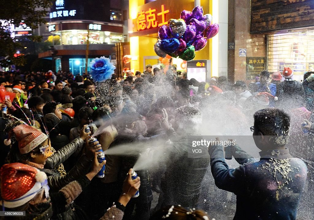 People enjoy a fight with foam spray during a celebration for the Christmas Eve on December 24, 2013 in Guiyang, China.