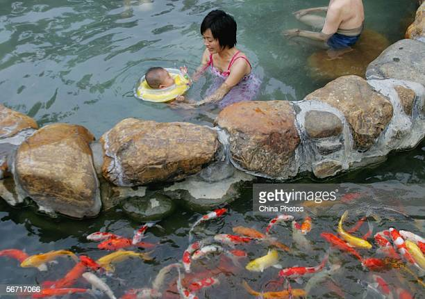 People enjoy a hot spring as fish swim in a lake at a resort on January 31 2006 in Qingyuan of Guangdong Province China Qingyuan is famous for its...