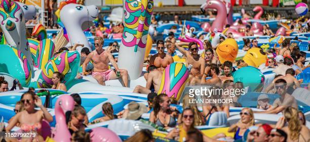 People enjoy a hot summer day on inflatable boats during the second edition of the Utrecht Drijf event in Utrecht The Netherlands on June 29 2019...