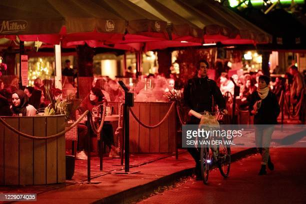 """People enjoy a last drink in bars before a partial lockdown in The Hague, on October 14, 2020. - The Netherlands goes into """"partial lockdown"""" at 10pm..."""