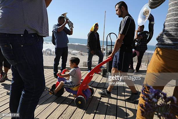 People enjoy a late afternoon near the USMexico border fence which ends in the Pacific Ocean on September 25 2016 in Tijuana Mexico Friendship Park...