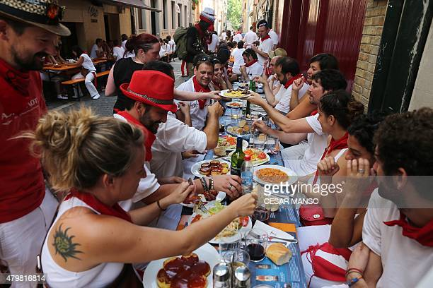 People enjoy a lunch in a street during the San Fermin Festival in Pamplona on July 7 2015 The festival is a symbol of Spanish culture that attracts...