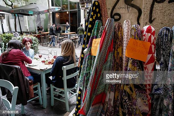People enjoy a meal at a cafebar next to a fabric store in the Agia Irini district of Athens Greece on Saturday April 25 2015 The downturn that...