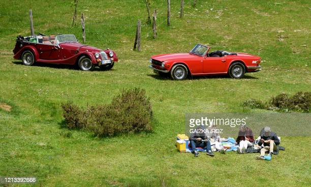 People enjoy a picnic on a meadow, with convertibles parked in the background, near Larrau, southwestern France, on May 17 on the first weekend after...