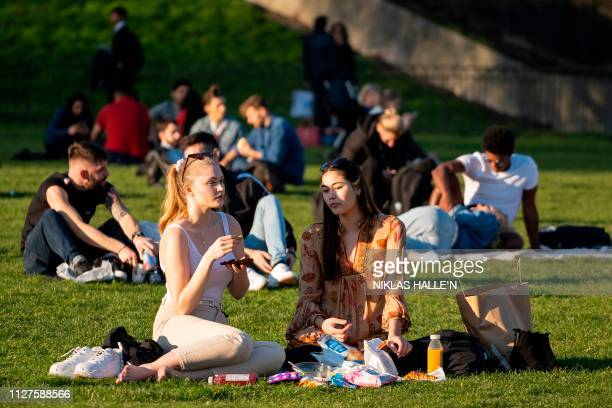 People enjoy a picnic on the grass as the sun shines in Green Park in central London on February 26 as Britain experienced record temperatures for a...