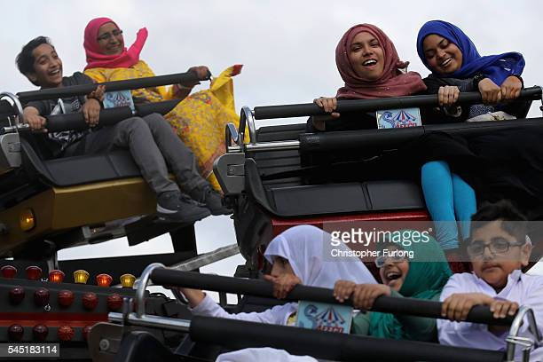 People enjoy a ride on the fun fair as they celebrate the festival of Eid in Small Heath Park on July 6 2016 in Birmingham England Up to 70000 people...