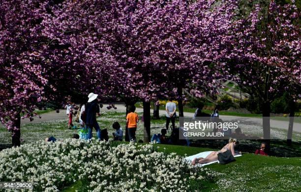 People enjoy a sun bath at the Parc Floral of the Bois de Vincennes in Paris on April 18, 2018.