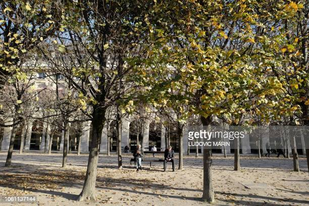 People enjoy a sunny afternoon in the Palais Royal garden on November 13 in Paris
