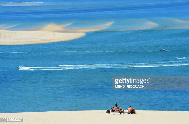 """People enjoy a sunny day atop Europe's tallest sand dune called """"Dune du Pilat"""" after its reopening in La Teste-de-Buch, near the Arcachon Bay on May..."""