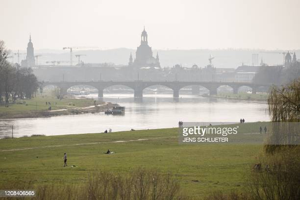 People enjoy a sunny day in a park on the banks of the river elbe in Dresden, eastern Germany, on March 27, 2020 amid the novel coronavirus pandemic.