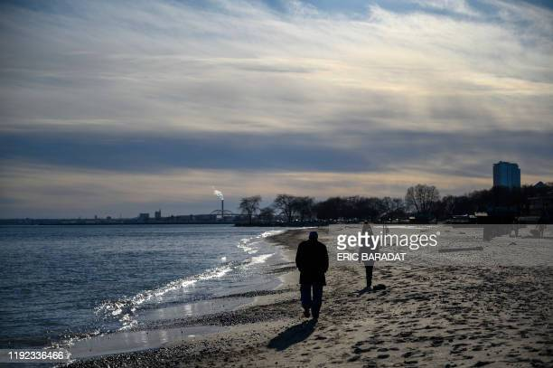 People enjoy a sunny winter day on the beach by Lake Michigan in Milwaukee, Wisconsin, on January 6, 2020. - The 2020 Democratic National Convention,...