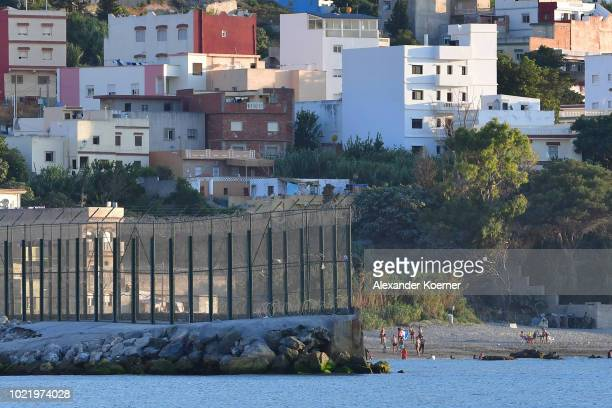 People enjoy a swim on the Moroccan site of the border fence separating the Spanish exclave of Ceuta from Morocco on August 23, 2018 in Ceuta, Spain....