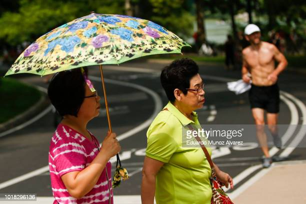 People enjoy a warm day at Central Park on August 17 2018 in New York City Severe thunderstorms and even an isolated tornado could strike New York...