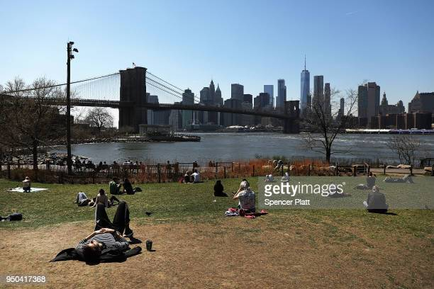 People enjoy a warm spring day with temperatures in the high 60's in the Dumbo section of Brooklyn on April 23 2018 in New York City After an...