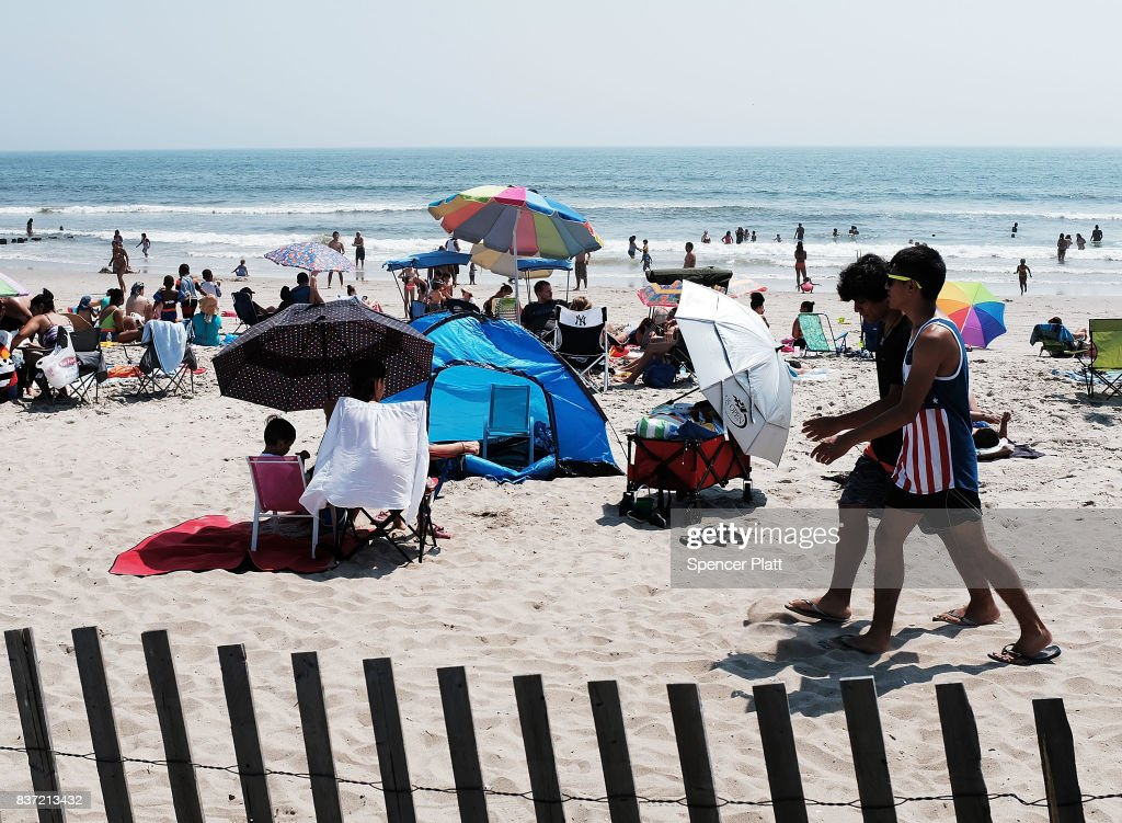 People enjoy an afternoon along Rockaway Beach on a hot summer day on August 22, 2017 in the Queens borough of New York City. New York and much of the Northeast is experiencing warm and muggy weather with temperatures in the 90's and a heat index of over 100.