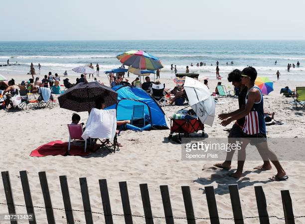 People enjoy an afternoon along Rockaway Beach on a hot summer day on August 22, 2017 in the Queens borough of New York City. New York and much of...