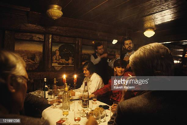 People enjoy an evening dining with musicians playing in a restaurant in the old part of Belgrade, Serbia, 25th December 1986.