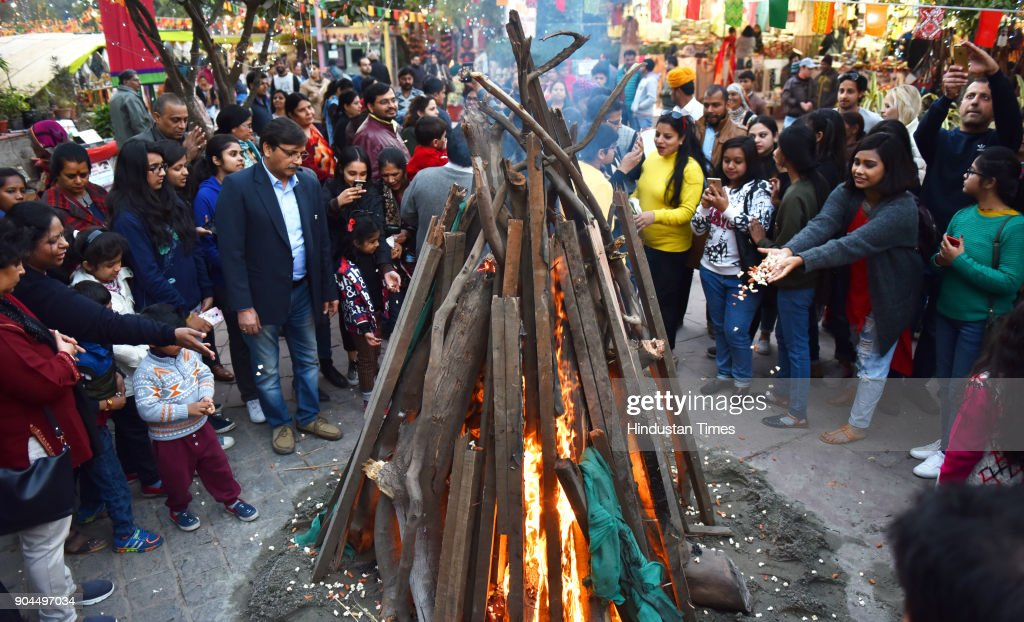 People enjoy as they celebrate Lohri festival at Dilli Haat, on January 13, 2018 in New Delhi, India. Lohri is a great occasion that holds great importance for farmers. The festival of harvest, Lohri is being celebrated in North India especially in Punjab, Haryana, Himachal Pradesh and Delhi. Popcorns, peanuts, Rewari and Gajak are distributed to all neighbours, friends and relatives on the occasion.