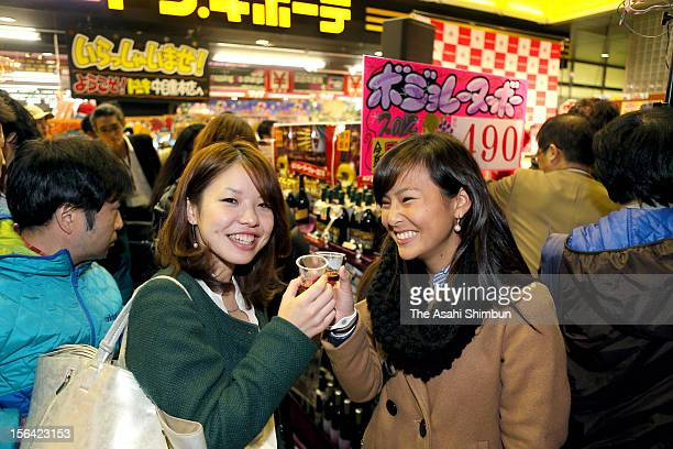 People enjoy Beaujolais Nouveau as the young French wine gets released just after midnight in front of a discount chain store Don Quijote which has...