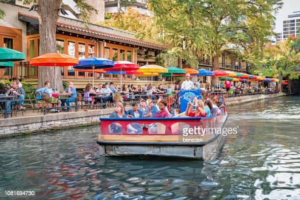 people enjoy boat tour on san antonio river texas usa - san antonio river walk stock photos and pictures