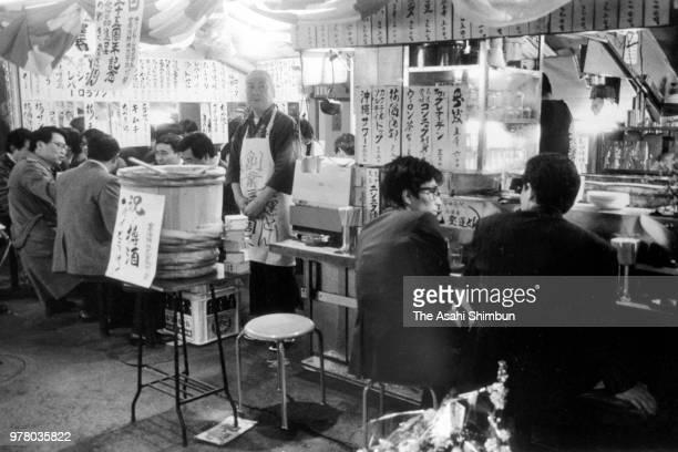 People enjoy drinking at an Izakaya pub under elevated railway tracks on December 1 1988 in Tokyo Japan
