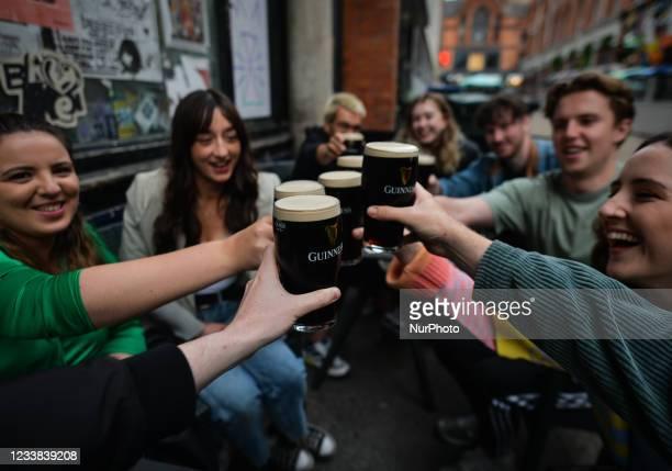 People enjoy drinking Guinness outside a pub in Dublin city center. On Monday, 05 July 2021, in Dublin, Ireland