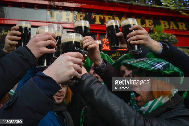 People enjoy drinking Guinness outside Temple Bar pub on the opening day of St Patrick's Day Festival On Friday March 15 in Dublin Ireland