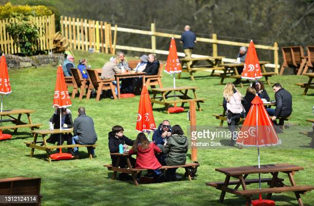 People enjoy food whilst in a beer garden at Hotel Rudyard on April 12, 2021 in Leek, England. England has taken a significant step in easing its...