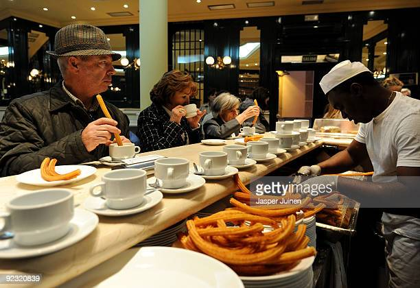 People enjoy freshly fried Churros at the San Gines Chocolateria on October 23 2009 in Madrid Spain The ridged crunchy fried dough pastry called...