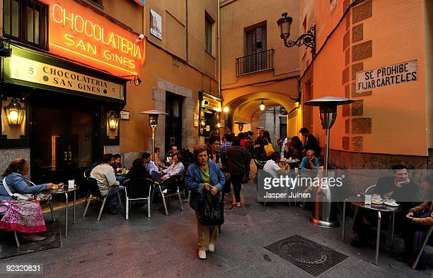 People enjoy freshly fried Churros on the terrace of the San Gines Chocolateria on October 23 2009 in Madrid Spain The ridged crunchy fried dough...