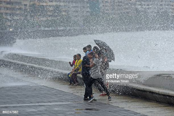 People enjoy high tide at Marine Drive on September 20 2017 in Mumbai India Torrential rain battered Mumbai and its suburbs for the second day on...