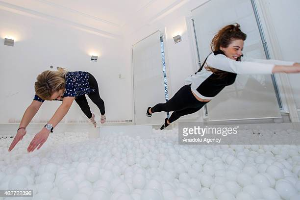 People enjoy 'Jump In' interactive art installation which is a 30person pit full of 81000 white balls made by west London creative agency...