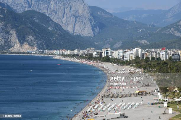 People enjoy Konyaalti beach on August 18, 2019 in Antalya, Turkey. Turkey's resort towns saw a 100 percent occupancy rate with the Eid al-Adha...