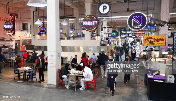 People enjoy lunch at Grand Central Market as indoor dining reopens in Los Angeles, on March 15, 2021. - Los Angeles and southern California is...