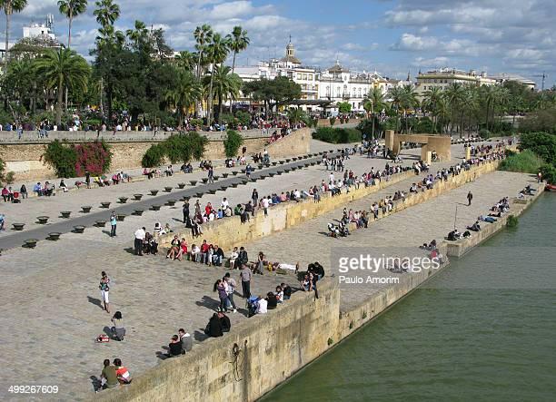 People enjoy next Guadalquivir river in Seville, Spain.