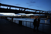 People enjoy on the banks of Thames river in London