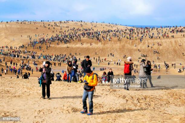 People enjoy Pokemon Go during the Pokemon GO Safari Zone at Tottori Sand Dune on November 24, 2017 in Tottori, Japan. For the first day of three-day...