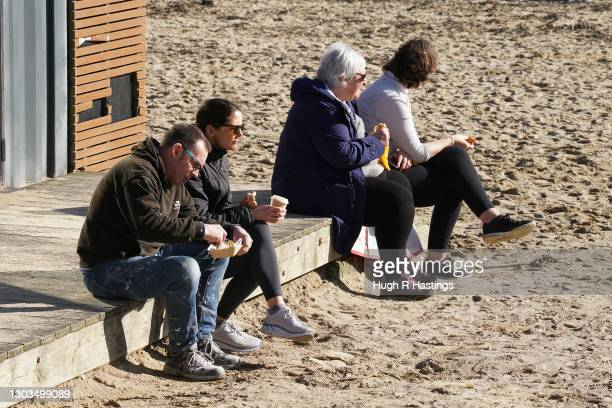 People enjoy refreshments on Gylllyngvase Beach on February 22, 2021 in Falmouth, United Kingdom. After a surge of Covid-19 cases, fueled partly by a...