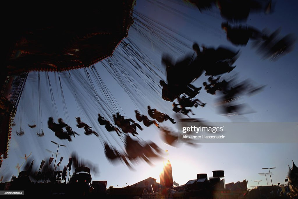 People enjoy riding on a merry-go-round on the opening day of the 2014 Oktoberfest at Theresienwiese on September 20, 2014 in Munich, Germany. The 181st Oktoberfest will be open to the public from September 20 through October 5 and traditionally draws millions of visitors from across the globe in the world's largest beer fest.