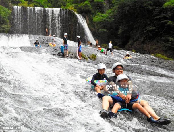 People enjoy sliding at RyumonnoTaki falls on July 22 2018 in Kokonoe Oita Japan Two highpressure systems are blanketing the Japanese archipelago at...
