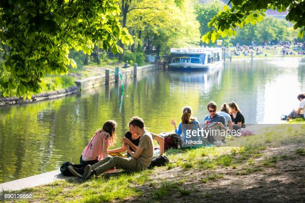 people enjoy sun at landwehrkanal in berlin kreuzberg - kreuzberg stock photos and pictures