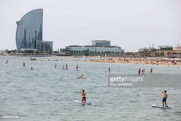 People enjoy surfing at the Barceloneta's beach, in Barcelona on June 12, 2016. / AFP / PAU BARRENA