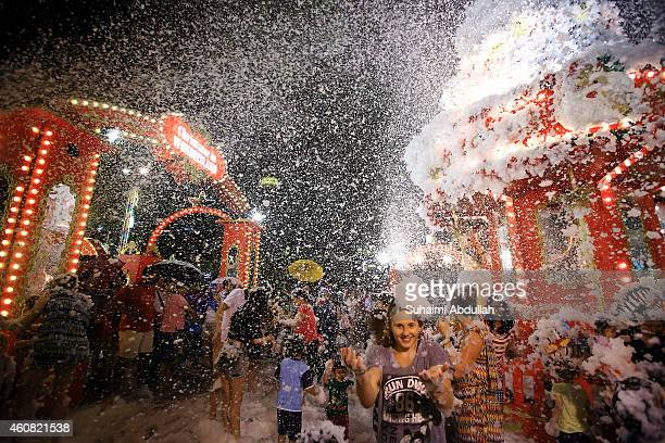 People enjoy the artificial snow made of foam at Tanglin Mall shopping centre on December 24 2014 in Singapore The mall has been holding the...
