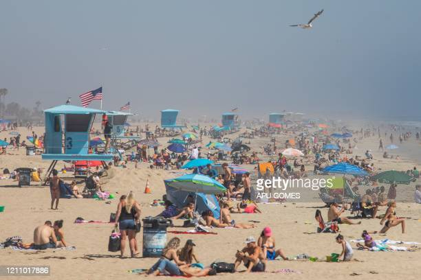 People enjoy the beach amid the novel coronavirus pandemic in Huntington Beach California on April 25 2020 Orange County is the only county in the...