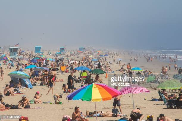 TOPSHOT People enjoy the beach amid the novel coronavirus pandemic in Huntington Beach California on April 25 2020 Orange County is the only county...