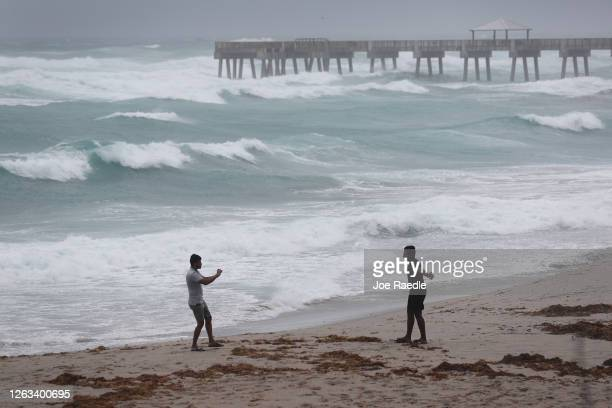 People enjoy the beach as waves crash ashore from Tropical Storm Isaias as it passes through the area on August 02, 2020 in Juno Beach, Florida. The...
