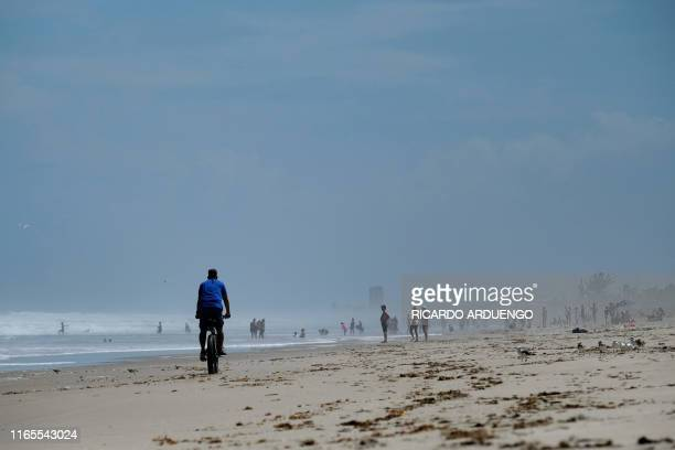 """People enjoy the beach in Melbourne, Florida as Hurricane Dorian approaches on September 1, 2019. - Hurricane Dorian unleashed """"catastrophic..."""