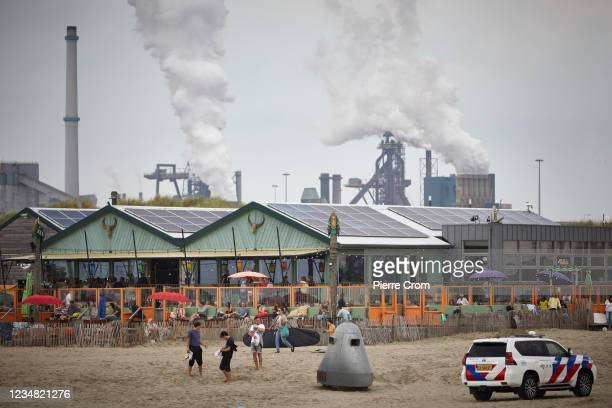 People enjoy the beach near the Tata Steel plant on August 21, 2021 in Velsen-Noord. The Tata steel plant is under investigation by the Dutch Public...