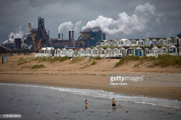 People enjoy the beach of Ijmuiden near the Tata Steel plant on August 22, 2021 in Ijmuiden. The Tata steel plant is under investigation by the Dutch...